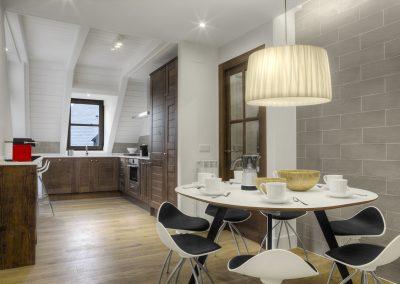 Cocina abierta, muebles de madera,barra desayuno, techo de madera pintada en blanco, iluminación indirecta: