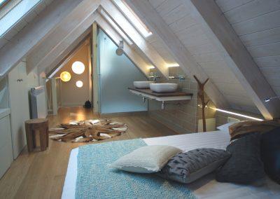 Suite bajo cubierta, techo madera blanca, dormitorio con baño: Reforma y decoración de vivienda en Baqueira (Valle de Arán-Pirineos)